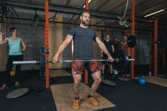 Gruppe Crossfit-Trainergewichtheben lizenzfreie stockfotos