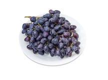 Gruppe der blauen Trauben auf einem weißen Teller Stockbilder