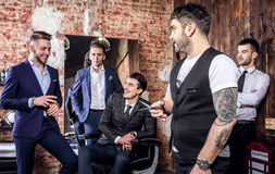 Gruppe der Haltung der jungen eleganten positiven Männer im Innenraum des Friseursalons Stockfotografie