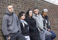 Gruppe der Jugend, die auf Wand sich lehnt stockfoto