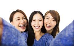 Gruppe der jungen Frau, die den Spaß zusammen nimmt selfie hat stockfoto