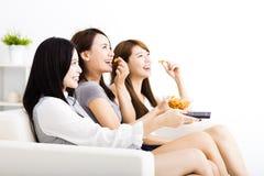 Gruppe der jungen Frau, die Snäcke isst und fernsieht Lizenzfreies Stockfoto