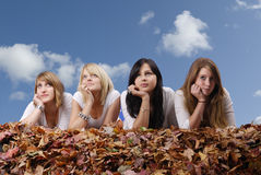 Gruppe der jungen Frau liegend in den Herbstblättern Lizenzfreies Stockfoto