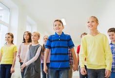 Gruppe der lächelnden Schule scherzt das Gehen in Korridor Lizenzfreie Stockfotos