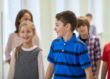 Gruppe der lächelnden Schule scherzt das Gehen in Korridor Stockfoto