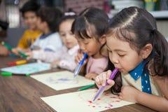 Gruppe der netten kleines Stiftmalerei des Mädchen- und Jungenstudenten Schlagfarbzusammen mit Kindergärtnerin in der Klassenzimm lizenzfreies stockfoto