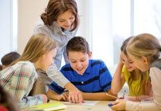Gruppe der Schule scherzt Schreibenstest im Klassenzimmer Stockfoto