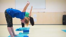 Gruppe der Seitenansicht A von drei Mädchen, die Übungen - Ausdehnungshandblaue Gummiexpander tun stock footage