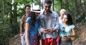 Gruppe der touristischen Kontrollkarte unter Verwendung des Zellintelligenten Telefons, das zusammen in Forest Mix Race People Se stock video footage