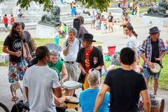 Gruppe des Afroamerikaners, lateinisch und kaukasische Schlagzeuger und Schlagzeuger, die Rhythmus an Tam Tams-Festival spielen stockfoto