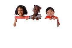 Gruppe des gemischtrassigen Kinderporträts mit weißem Brett Getrennt lizenzfreie stockfotos