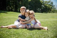 Gruppe des glücklichen kleine Kinderlächelnden Sitzens im Park auf Gras Freundschaft, Kindheit, Ferien lizenzfreie stockbilder