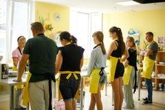 Gruppe des hörenden Frauenchefs der Studenten, der Lektion kocht lizenzfreie stockfotografie