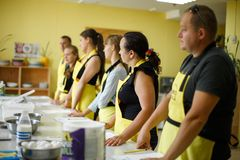 Gruppe des hörenden Frauenchefs der Studenten, der Lektion kocht stockfoto