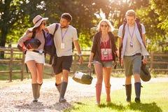 Gruppe des junge Leute-gehenden Kampierens am Musik-Festival lizenzfreies stockbild
