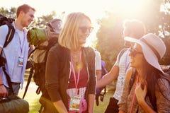 Gruppe des junge Leute-gehenden Kampierens am Musik-Festival stockfotografie