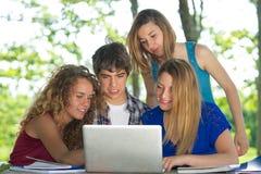 Gruppe des jungen Kursteilnehmers, der den Laptop im Freien verwendet lizenzfreie stockbilder