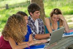Gruppe des jungen Kursteilnehmers, der den Laptop im Freien verwendet stockfotos