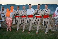 Gruppe des jungen Mannes die traditionelle Ausstattungsaufstellung tragend stockfoto