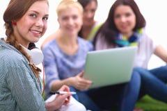 Gruppe des jungen Studenten sitzend auf grünem Gras Lizenzfreie Stockfotografie