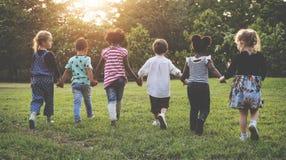 Gruppe des Kindergartens scherzt das Freundhändchenhalten, das am Park spielt stockbild