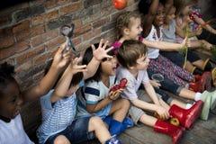 Gruppe des Kindergartens scherzt die kleinen Landwirte, welche die Gartenarbeit lernen stockbild