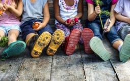 Gruppe des Kindergartens scherzt die kleinen Landwirte, welche die Gartenarbeit lernen lizenzfreies stockbild