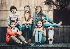 Gruppe des Kinderporträts mit Ball und Skateboard stockbilder