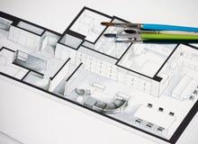 Gruppe des klaren bunten Bürstensatzes auf architektonischem isometrischem Handzeichen des Immobiliengrundrisses Stockfotografie