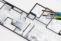 Gruppe des klaren bunten Bürstensatzes auf architektonischem isometrischem Handzeichen des Immobiliengrundrisses Lizenzfreie Stockbilder