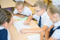 Gruppe des Klassenzimmers der Schulkinder in der Schule, das am Schreibtisch sitzt Stockfoto