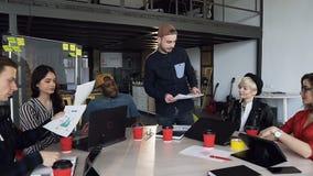 Gruppe des kreativen, multi ethnischen Teams der Geschäftsleute in zufälligen clothingexchange Erfahrungen und in der Wissensanwe stock footage