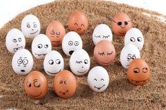 Gruppe des lustigen verrückten Lächelns eggs auf einem Sand Stockfotografie