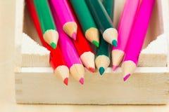 Gruppe des Scharfen färbte Bleistifte mit hölzernem Hintergrund Stockfotos
