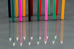 Gruppe des Scharfen färbte Bleistifte mit Reflexionen auf Dunkelheit Stockfotos