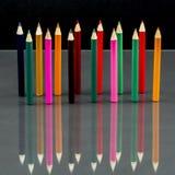 Gruppe des Scharfen färbte Bleistifte mit Reflexionen auf Dunkelheit Stockfoto
