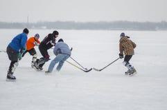 Gruppe des unterschiedlichen gealterten Leutespielens hokey auf einem gefrorenen Fluss Dnipro in Ukraine Lizenzfreies Stockbild