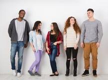 Gruppe des verschiedenen Studentenschlangestehens zuhause Stockbild