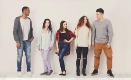 Gruppe des verschiedenen Studentenschlangestehens zuhause Stockfoto