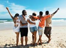 Gruppe des Zujubelns von jungen Erwachsenen am Strand stockfotografie