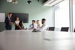 Gruppe, die auf Aufgabe am graduierten Einstellungs-Einschätzungs-Tag zusammenarbeitet, während, beobachtend vom Einstellungs-Tea stockfotografie