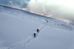 Gruppe, die auf schneebedeckten Bergen im Winter wandert Stockbilder