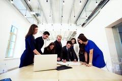 Gruppe, die junge wohlhabende Geschäftsleute in der Unternehmenskleidung zusammenarbeitet im Team auf Gemeinschaftsprojekten ist, stockfoto