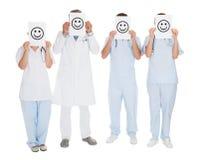 Gruppe Doktoren, die smileyikone halten Lizenzfreie Stockbilder