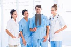 Gruppe Doktoren und Chirurgen, die Röntgenstrahl überprüfen stockfoto