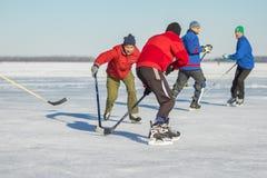 Gruppe einfachen Leute, die Hockey auf einem gefrorenen Fluss Dnepr in Ukraine spielen Stockbilder