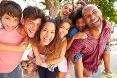 Gruppe Eltern, die Kinder geben, tragen Fahrt draußen huckepack Lizenzfreies Stockfoto