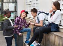 Gruppe entspannende und plaudernde Jugendfreunde Lizenzfreie Stockbilder
