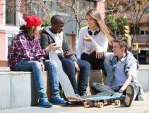 Gruppe entspannende und plaudernde Jugendfreunde Stockfotos