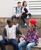 Gruppe entspannende und plaudernde Jugendfreunde Lizenzfreies Stockfoto